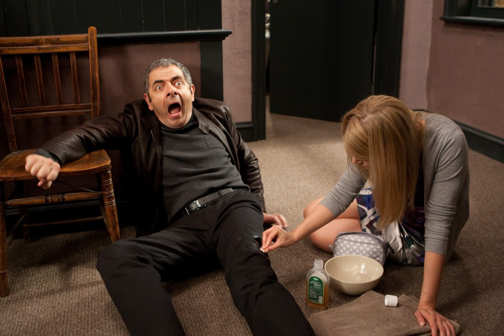 """In this film image released by Universal Pictures, Rowan Atkinson, left, and Rosamund Pike are shown in a scene from """"Johnny English Reborn"""". (AP Photo/Universal Pictures, Giles Keyte)"""